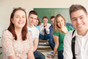 Happy students sitting on tables in a classroom