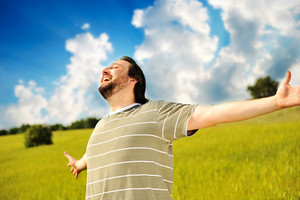 Happy succesful man in nature with wide open arms
