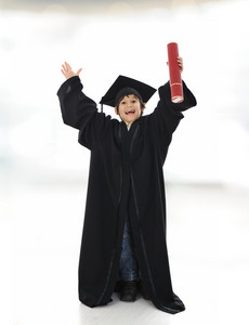 Happy successful kid with diploma and graduating clothes