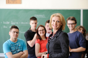 Happy teacher standing in a classroom in front of her smiling students