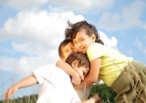 Happy three kids huging each other outdoor
