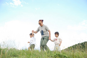 Happy two children in nature with grandmother runing