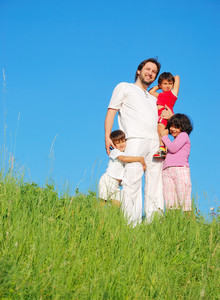 Happy unforgetable childhood on green meadow against blue sky