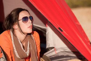 Happy woman camping lying and relaxing in tent alone