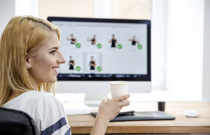 Happy woman holding cup with coffee in office