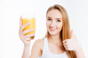 Happy woman holding glass with fresh kuice and showing thumb up isolated on a white background