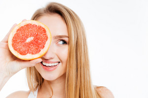 Happy woman holding slice of grapefruit isolated on a white background
