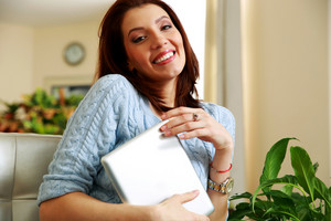 Happy woman holding tablet computer at home