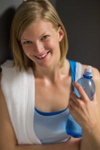 Happy woman holding water bottle in locker room at gym