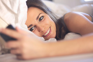 Happy woman lying on bed smiling while reading a text message from someone