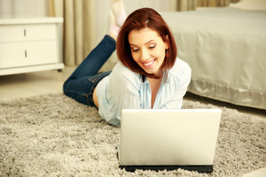 Happy woman lying on the floor and using laptop at home