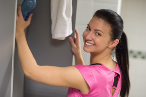 Happy woman putting water bottle in locker at gym