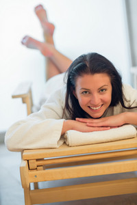 Happy woman relaxing on wooden bed at beauty spa