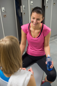Happy woman sitting opposite friend in changing room at healthclub