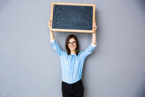 Happy woman standing with billboard over gray background. Wearing in blue shirt and glasses. Looking at camera