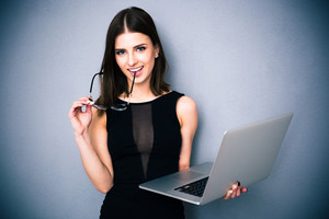 Happy woman standing with laptop and glasses