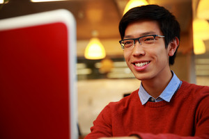 Happy young asian man looking at laptop screen