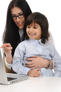 Happy young beautiful mother and cute little son on laptop at the table