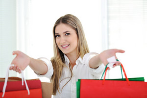 Happy young blonde woman holding shopping bags