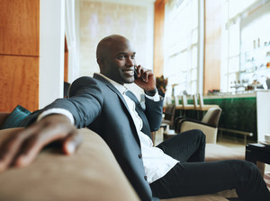 Happy young businessman sitting relaxed on sofa at hotel lobby making a phone call, waiting for someone.