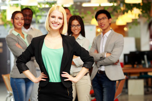 Happy young businesswoman standing in front of colleagues at office