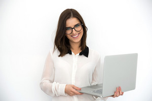 Happy young businesswoman standing with laptop