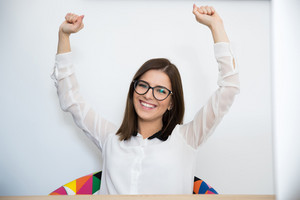 Happy young businesswoman with arms raised up