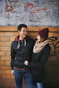Happy young couple looking at each other against a wall. Teenage asian man and woman in love spending time together outdoors.