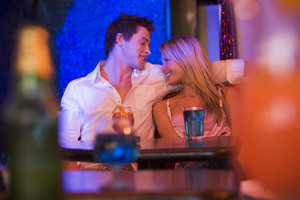 Happy young couple sitting in a nightclub, smiling at each other