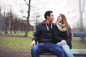 Happy young couple sitting on a bench outdoors during winter season. Asian teenage couple in warm clothes sitting on park bench.