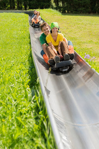 Happy young couples enjoying alpine coaster luge during summer