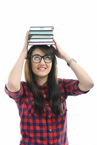 Happy young girl with glasses isolated on white holding books on her head