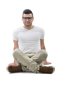 Happy young guy with glasses sitting on the floor
