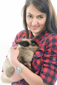 Happy young handsome caucasian girl with checkered shirt isolated on white holding a rabbit