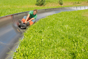 Happy young man enjoying alpine coaster luge during summer