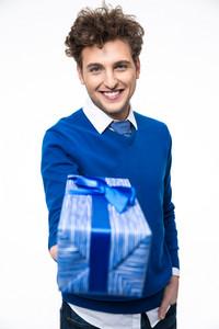 Happy young man giving gift at camera