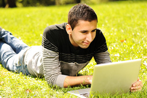 Happy young man laying on green grass in nature and working on laptop