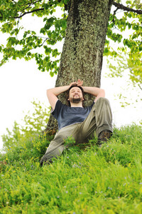 Happy young man resting under the tree