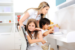 Happy young mother with her kids at children room