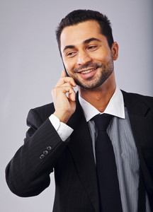 Happy young professional smiling while answering a phone call