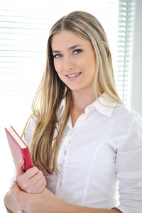 Happy young woman holding an red book and smiling