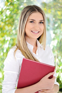 Happy young woman holding an red book