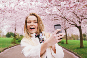 Happy young woman photographing herself using her mobile phone. Caucasian female talking selfie with her smart phone at park.