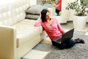 Happy young woman sitting on the floor with laptop at home