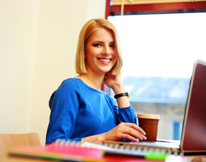 Happy young woman using laptop and looking at camera