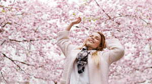 Happy young woman with her arms raised enjoying fresh air at spring blossom park. Caucasian female enjoying springtime.