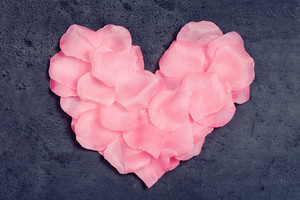 Heart of rose petals textile on gray background