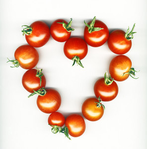 Heart Shape Made From Cherry Tomatoes Over White Background