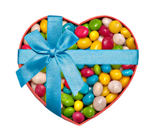 Heart-shaped box filled with colorful candies and tied with blue ribbon and bow