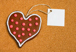 Heart shaped cookie with card on cork surface